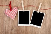 Blank instant photos and red heart hanging. On wooden background
