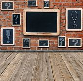 Question marks and exclamation marks white chalk drawing on small blackboard hanging in old room and