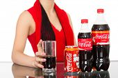 NAKHODKA, RUSSIA - JANUARY 18, 2014: Asian young girl pours a Coca-Cola from a bottles into a glass. Coca-Cola is a carbonated soft drink sold in stores, restaurants, and vending machines worldwide