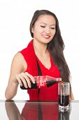 NAKHODKA, RUSSIA - JANUARY 18, 2014: Cheerful Asian girl pours a Coca-Cola from a bottle into a glas