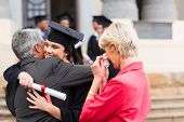 picture of graduation gown  - beautiful young female graduate hugging her father at graduation - JPG