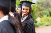 pretty african university graduate looking back at graduation ceremony
