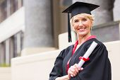 happy middle aged woman with graduation cap and gown holding diploma