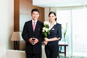 Hotel Manager or director and supervisor welcome arriving VIP guests with roses on arrival in luxury