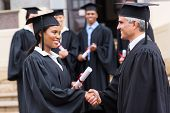 smiling afro american female graduate handshaking with dean