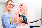 Female cleaner in laundry shop or textile dry-cleaning ironing jacket by hand with iron