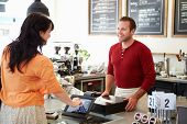 stock photo of cash  - Customer Paying In Coffee Shop Using Touchscreen - JPG
