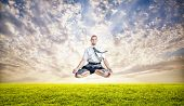 image of levitation  - Businessman doing Yoga meditation and levitating under the green grass at sunset sky - JPG