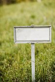 Blank sign board on a field