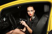 Fashionable woman smoking a cigarette in a car