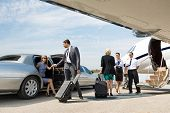 stock photo of stretching  - Business partners about to board private jet while airhostess and pilot greeting them - JPG