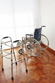 Empty wheelchair and wallker in nursing home as symbol for death