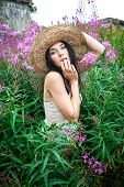 picture of nu  - Portrait of a girl in straw hat against nature and old wall background - JPG