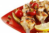 fresh grilled chicken shish kebab served wtih tomato cherry hot peppers on skewers over red plate is