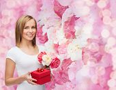 holidays, love and flowers concept - young woman with bouquet of flowers and red gift box