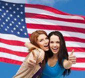 friendship and happy people concept - two smiling girls showing thumbs up over american flag backgro