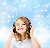 home, leisure, new technology and music concept - smiling little girl with headphones over blue sky