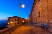 Benches on narrow illuminated cobbled street early in the morning in small italian town.