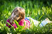 Portrait of little girl in the grass outdoors.