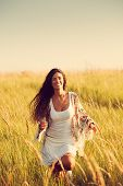 woman wearing boho style clothes run through the grass, summer day, retro colors