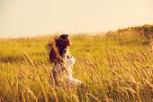 happy smiling woman wearing boho style clothes run through the grass, summer day