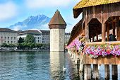 LUCERNE, SWITZERLAND - JULY 2, 2014: Chapel Bridge and Water Tower, Lucerne. The wooden covered bridge spans the Reuss River with the with Mt. Pilauts rising in the background.