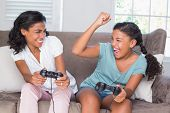 Happy mother and daughter playing video games together on sofa at home in living room