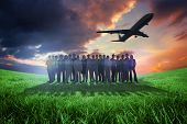 Business people standing up with airplane against green field under orange sky