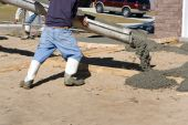 picture of chute  - Construction worker directs a chute to pour concrete for a driveway at a new home site - JPG