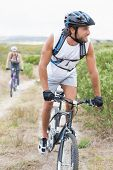 Fit attractive couple cycling on mountain trail on a sunny day