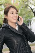 Smiling Asian young woman take a call, closeup portrait in outdoor.