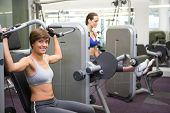 Healthy happy brunette using weights machine for arms at the gym