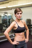Fit brunette in black sports bra looking at camera at the gym