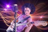 Pretty girl playing guitar against curved laser light design in orange