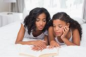 Mother and daughter reading book together on bed at home in bedroom