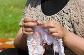 image of knitting  - woman knits knitting needles rare knitted fabrics in white thread - JPG