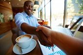 Image of cup of latte and business document and handshaking of business partners in cafe