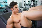 Side view of male weightlifter doing leg presses in gym
