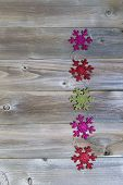 Holiday Snowflake Shaped Ornaments On Weathered Wood