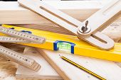 picture of carpenter  - Close up view of a colorful yellow carpenters level ruler and right angle lying on planks of new hardwood together with a pencil for measurements in a carpentry construction DIY and joinery concept - JPG