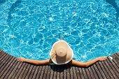 Woman with big hat relaxing on the swimming pool