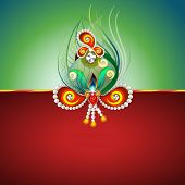 Beautiful peacock feather and pearls decorated rakhi on green and red background for Raksha Bandhan