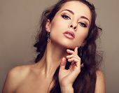 Sexy Woman In Fashion Earrings Touching Clean Face. Closeup