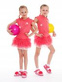 Two young girl gymnast with sports balls.