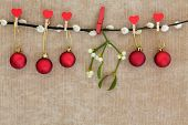 stock photo of pussy-willows  - Christmas red bauble decorations with mistletoe leaf sprig hanging on a pussy willow branch over brown paper background - JPG