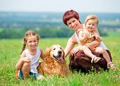 Mother and her two daughters in the park with a golden retriever dog