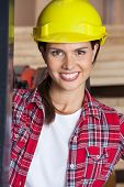 Closeup portrait of confident female engineer wearing hardhat in workshop