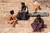 Sadhu Sits On The Ghat Along The Ganges River In Varanasi, India.