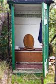 stock photo of outhouses  - Open old wooden outhouse in the garden - JPG