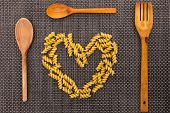 Heart made from fusilli with wooden fork and spoons